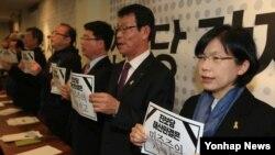 한국 통합진보당 이정희 전 대표(오른쪽)가 22일 서울 정동 프란치스코회관에서 열린 '통합진보당 강제해산에 따른 3차 비상 원탁회의'에 참석해 손팻말을 든 채 구호를 외치고 있다.