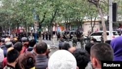 Warga menyaksikan polisi mengosongkan jalanan setelah ledakan di Urumqi, Xinjiang (22/5).