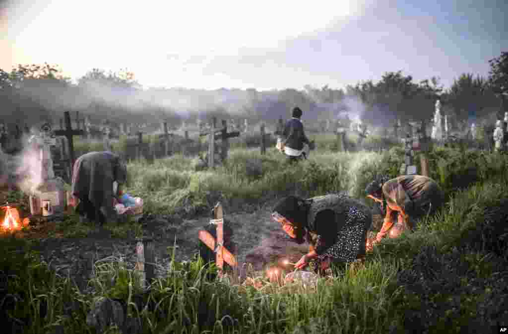 Women observing religious rites light fires next to graves in the village of Copaciu, southern Romania, ahead of Orthodox Easter, celebrated this year on May 1.