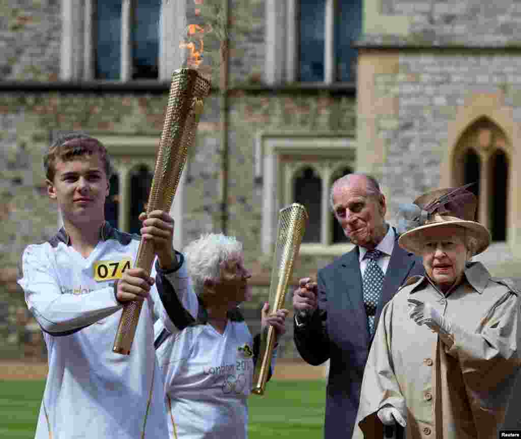 Britain's Queen Elizabeth (R), Prince Philip (2nd R), and Olympic torch bearer Gina Macgregor (2nd L) watch as torchbearer Phil Wells takes the Olympic Flame at Windsor Castle, west of London July 10, 2012.