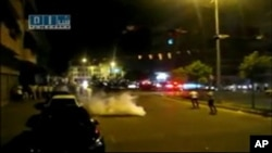 Syrian protesters run after tear gas canisters are thrown in al-Malaab street in Homs, 165 km (100 miles) north of Damascus, in this still image taken from video posted on a social media website, August 4, 2011 (Reuters cannot independently verify the con