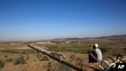 Čovek prati situaciju na sirijskoj strani Golanske visoravni