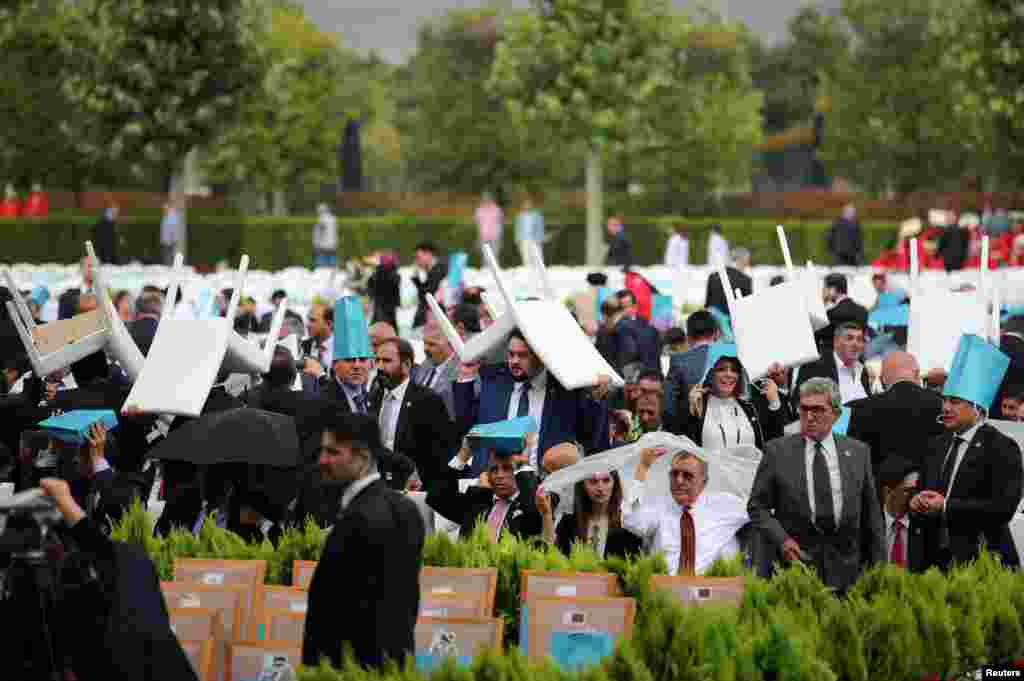 Invitees take cover from the rain as they wait for arrival of Turkish President Tayyip Erdogan during a ceremony at the Presidential Palace in Ankara.