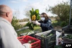 Seorang warga mengisi keranjang khusus anggota AMAP dengan sayuran di Campbon, Perancis, 2 April 2020.