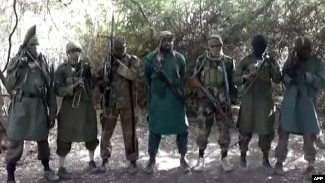 A picture taken from a video reportedly shows Abubakar Shekau (C), the suspected leader of Nigerian Islamist extremist group Boko Haram, flanked by six armed and hooded fighters in an undisclosed place, March 5, 2013.