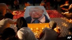 Warga di Singapura menyalakan lilin dekat foto mendiang Lee Kuan Yew sebagai penghormatan (27/3). (AP/Wong Maye-E)