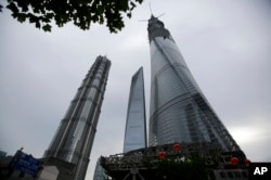 The Shanghai Tower, right, is seen among other skyscrapers prior to the topping off ceremony in Shanghai, China, Saturday, Aug. 3, 2013.