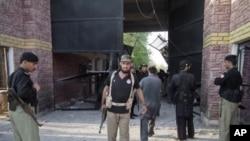 Cảnh sát đứng cạnh cổng trại giam đã bị hư hại sau khi các tù nhân trốn thoát