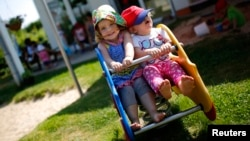 FILE - Two toddlers enjoy a ride at a child care site near Frankfurt, Germany. A new study says tykes can become more persistent in pursuing a goal if they've just seen an adult struggle at a task before succeeding.