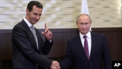 FILE - Russian President Vladimir Putin, right, shakes hands with Syrian President Bashar Assad in the Black Sea resort of Sochi, Russia, Nov. 20, 2017.