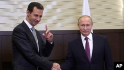 FILE - Russian President Vladimir Putin (R) shakes hands with Syrian President Bashar Assad in the Black Sea resort of Sochi, Russia, Nov. 20, 2017.