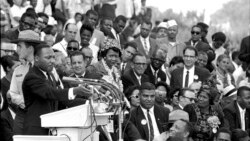"مارتن لوثەر کینگ لە میانەی پـێشکەشکردنی وتارەکەی لە واشنتنی پایتەخت لە 28 ی مانگی هەشتی ساڵی 1963. لەو وتارەدا گوتی""من خەونێکم هەیە"""