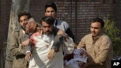 Orang-orang menolong seorang korban serangan di sebuah Mesjid Syiah di Peshawar, Pakistan (13/2). Taliban mengaku bertanggungjawab atas serangan yang setidaknya menewaskan19 orang itu.