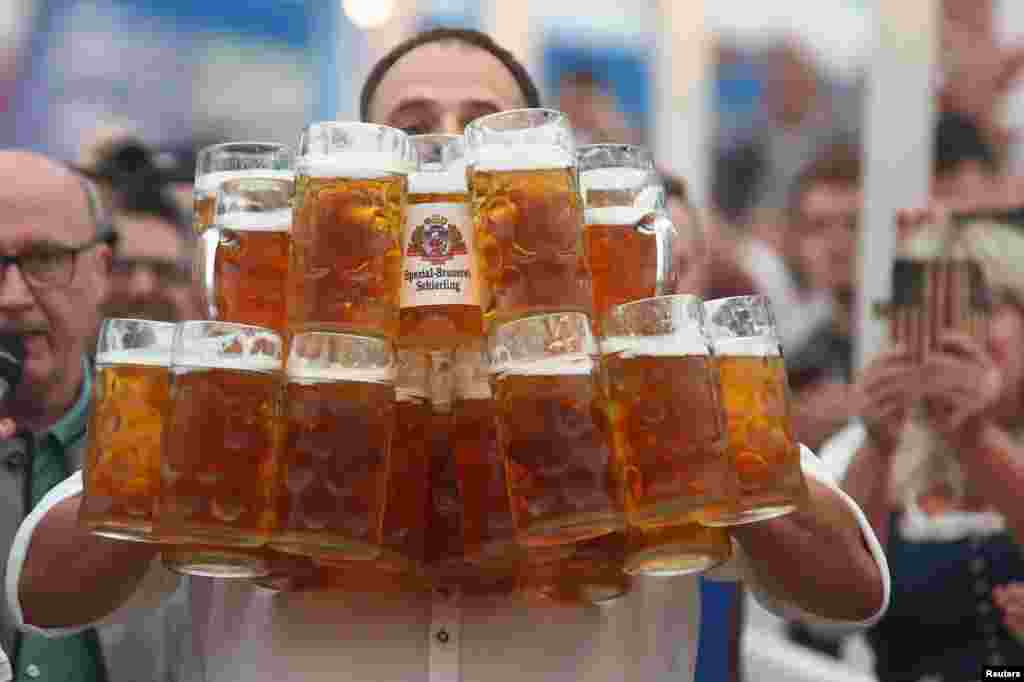 German Oliver Struempfel competes to set a new world record in carrying one liter beer mugs over a distance of 40 m (131 ft 3 in) in Abensberg, Germany September 3, 2017.