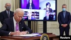 Presiden AS Joe Biden menandatangani perintah eksekutif terkait penanganan COVID-19 didampingi Dr. Anthony Fauci dan Jeff Zients listen di Gedung Putih (foto: dok0.
