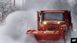Highway crews work to clear snow from roads in Henniker, New Hampshire, Jan. 2, 2014.