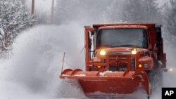 Petugas membersihkan salju dari sebuah jalan utama di kota Henniker, negara bagian New Hampshire, di timur laut wilayah AS, Kamis (2/1).