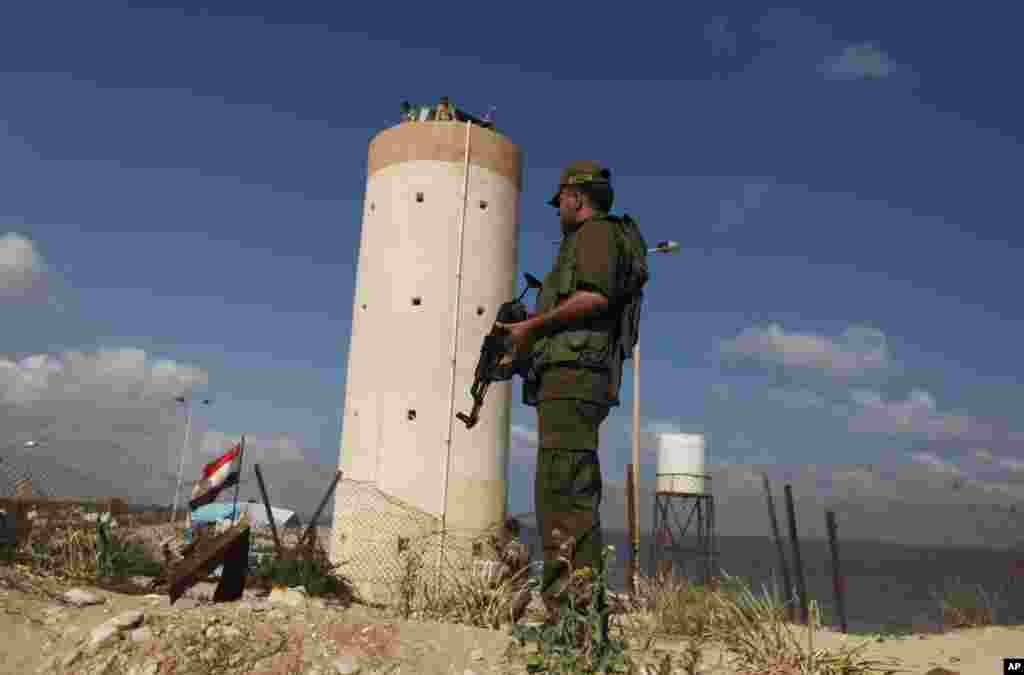 Palestinian Hamas security guard stands near an Egyptian watch tower on the border with Egypt in Rafah, southern Gaza Strip, July 5, 2013. An Egyptian official said the country's border crossing with Gaza Strip in northern Sinai has been closed indefinitely.