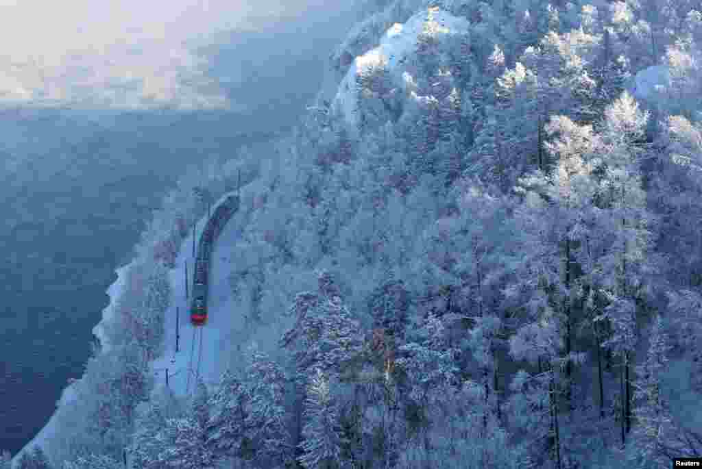 A passenger train moves along the bank of the Yenisei River in the Siberian Taiga forest covered with snow and hoarfrost outside Krasnoyarsk, Russia.