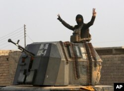 A member of Iraq's elite counterterrorism forces in a military convoy flashes a victory sign as forces advance toward Islamic State positions in the village of Tob Zawa, about 9 kilometers (5½ miles) from Mosul, Iraq, Oct. 25, 2016.
