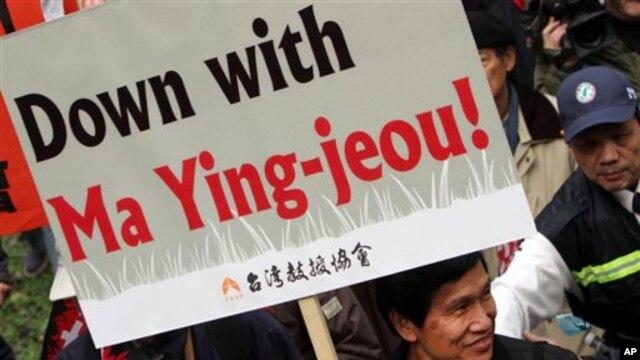 Seorang demonstran membawa spanduk yang menyerukan mundurnya Presiden Ma dalam protes di Taipei menentang kebijakan-kebijakan ekonominya hari Minggu (13/1).