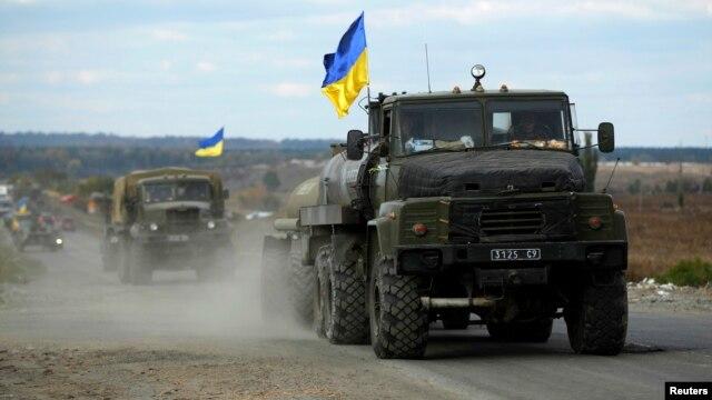 A Ukrainian military convoy moves on the road near the eastern Ukrainian town of Slovyansk, Oct. 5, 2014.