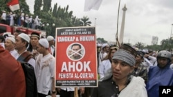 "A Muslim man hold a poster during a rally against Jakarta's minority Christian Governor Basuki ""Ahok"" Tjahaja Purnama who is being prosecuted for blasphemy, at the National Monument in Jakarta, Indonesia, Friday, Dec. 2, 2016."