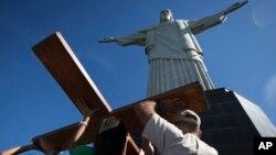 Người Công giáo mang chiếc thánh giá chuẩn bị cho Ngày Giới trẻ Thế giới. Bên trên là Tượng Chúa Kitô Cứu Thế ở Rio de Janeiro, Brazil