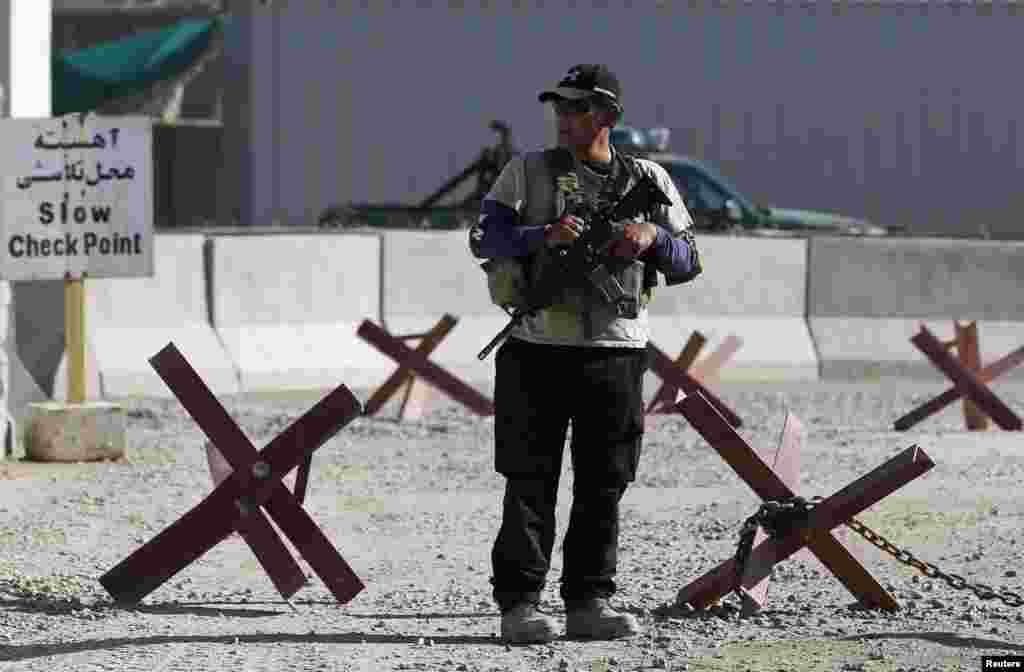 A foreign security contractor keeps watch at the site of a suicide attack, outside the counter-narcotics office near the Kabul International Airport, July 22, 2014.