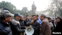 Lực lượng công an dùng loa phóng thanh kêu gọi giải tán biểu tình.