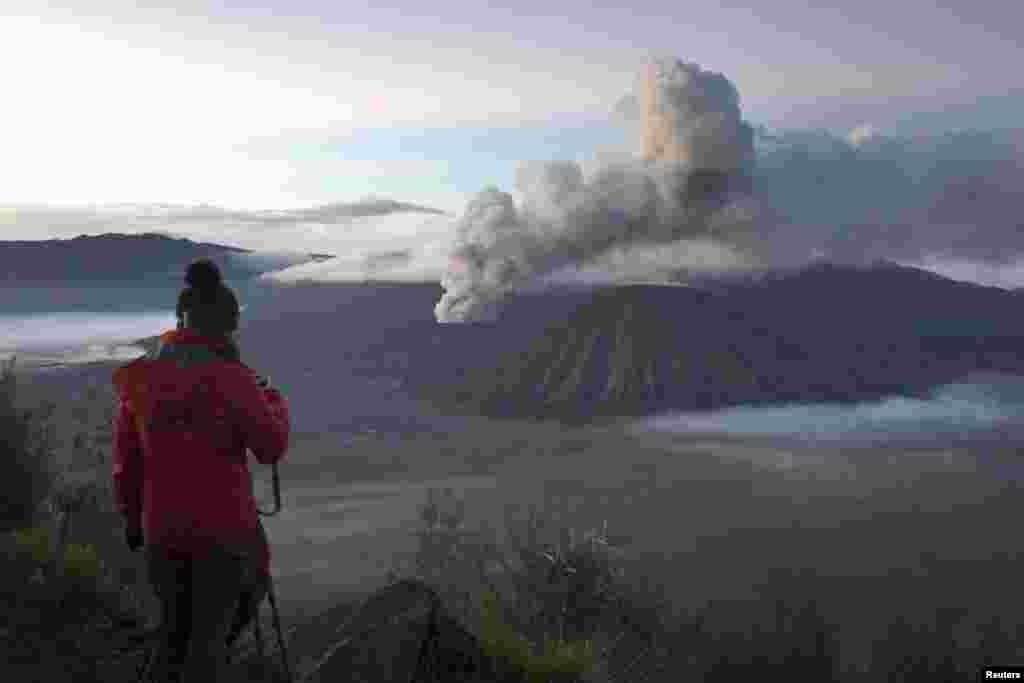 A visitor takes photographs of Mount Bromo, an active volcano and popular tourist destination, in Probolinggo, East Java province, Indonesia, in this photo taken by Antara Foto.
