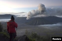 FILE - A visitor takes photographs of Mount Bromo, an active volcano and popular tourist destination, in Probolinggo, East Java province, Indonesia, April 3, 2016 in this photo taken by Antara Foto.