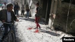阿勒颇居民走过被政府军空袭后的现场和血迹。(2016年10月12日)