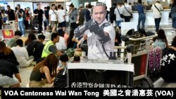 8月14日香港國際機場反送中集會,示威者展示一名曾經用槍指向示威者的警員的紙板人像 (攝影:美國之音湯惠芸)