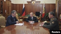 Russian President Vladimir Putin (C) speaks with newly appointed armed forces Chief-of-Staff Valery Gerasimov (R) and Defense Minister Sergei Shoigu during their meeting in Moscow's Kremlin, November 9, 2012.