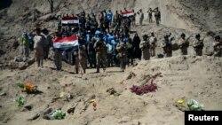 Tentara Irak berkumpul di kuburan massal tentara Syiah dari Kamp Speicher yang tewas akibat militan ISIS di kompleks mantan presiden Irak Saddam Hussein di Tikrit, 6 April 2015.