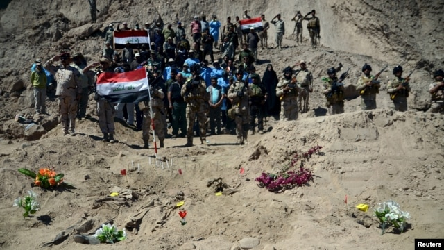 Iraqi soldiers salute next to a mass grave for Shi'ite soldiers from Camp Speicher who were killed by Islamic State militants in Tikrit, April 6, 2015.