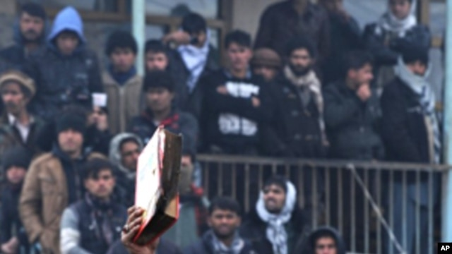 An Afghan demonstrator holds a copy of a half-burnt Quran, allegedly set on fire by US soldiers, at the gate of Bagram airbase during a protest against Koran desecration at Bagram, about 60 kilometers (40 miles) north of Kabul, February 21, 2012.