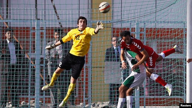 Pakistan's goalkeeper Saqib Hanif (L) jumps to make a save during a friendly football match against Afghanistan in Kabul, Afghanistan, Aug. 20, 2013.