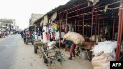 Un grossiste transporte un sac de vêtements de seconde main à son stand du marché de Colobane, le plus grand marché de vêtements de seconde main de la capitale sénégalaise, le 25 juin 2019.