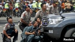 Police officers react near the site of a blast in Jakarta, Indonesia, January 14, 2016. Several explosions went off and gunfire broke out in the centre of the Indonesian capital on Thursday and police said they suspected a suicide bomber was responsible f
