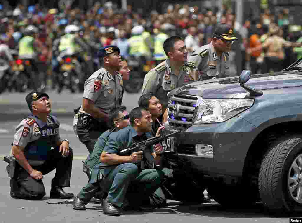 Police officers take a position behind a vehicle near the site of a blast in Jakarta, Indonesia. Several explosions went off and gunfire broke out in the center of the capital, leaving seven people dead, including all five attackers. The Islamic State group claimed responsibility for coordinated bomb and gun attack.