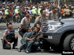 Police officers react near the site of a blast in Jakarta, Indonesia, Jan. 14, 2016.