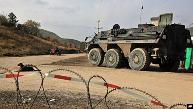 German troops serving in the NATO-led peacekeeping mission in Kosovo patrol near the Serb erected barricade in the village of Zupce, October 26, 2011.