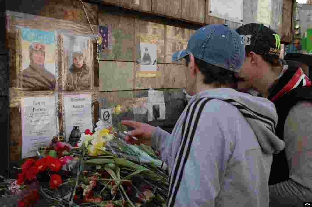 Visitors to Maidan look at a makeshift memorial for two of the more than 100 people killed in anti-government protests earlier this year. (Steve Herman/VOA)
