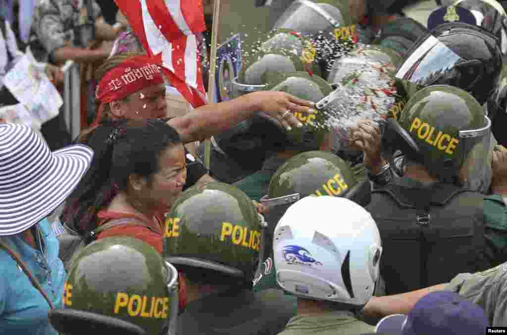 Một phụ nữ ném muối và ớt vào cảnh sát chặn đường tại Phnom Penh, Campuchia. Cư dân Boeung Kak Lake can dự vào vụ tranh chấp đất đai lâu ngày với một xí nghiệp xây dựng nhà cửa ở thủ đô.