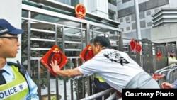 香港人权团体抗议后在中联办外贴挥春(苹果日报图片 )