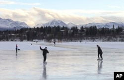 FILE - In this Jan. 2, 2018, file photo, ice skaters take advantage of unseasonable warm temperatures to ice skate outside at Westchester Lagoon in Anchorage, Alaska.