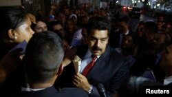 Venezuela's President Nicolas Maduro (C) greets supporters after his meeting with representatives of the Venezuelan coalition of opposition parties Mesa de la Unidad (MUD) and the Union of South American Nations' foreign ministers in Caracas, April 8, 201