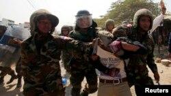 Một công nhân dệt may bị bắt trong cuộc biểu tình ở ngoại ô Phnom Penh.